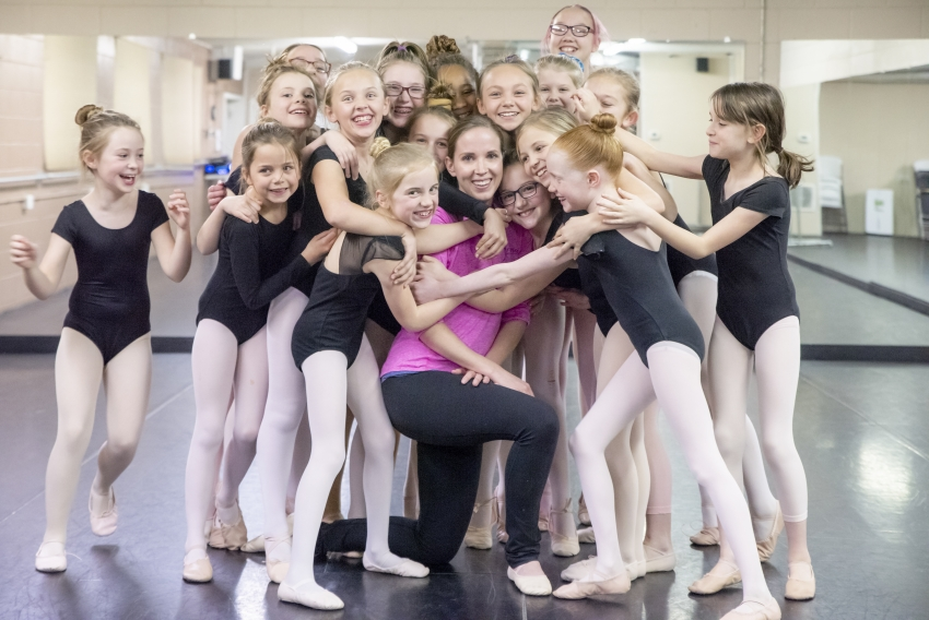 Dancers hugging teacher
